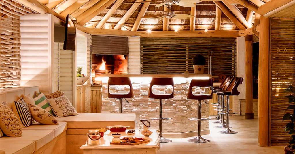 Thatched roof entertainment area with a built in fireplace