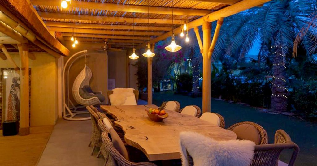 An exclusive outdoor living space with timber pergola and thatched roof structure.