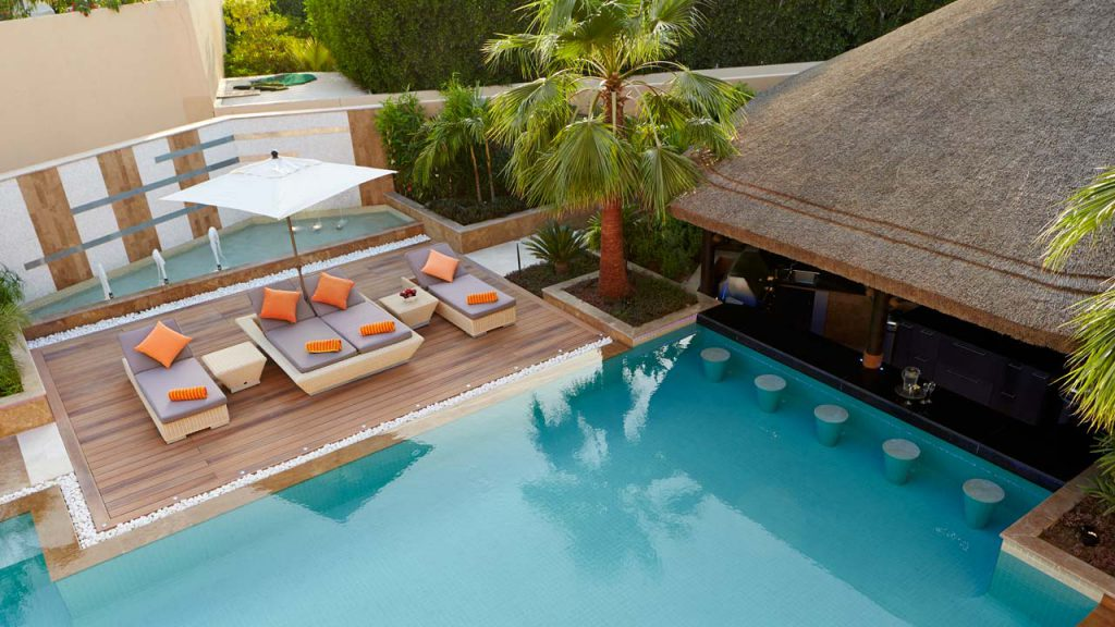 Sunken thatched gazebo with swim-up pool bar and decking.