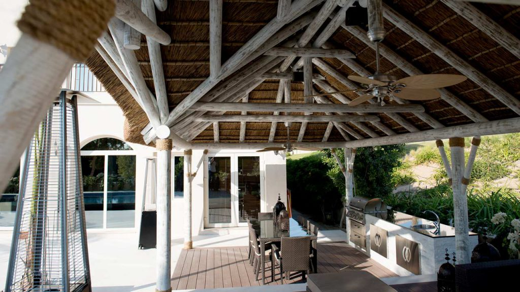Interior view of a white wash timber and thatch outdoor kitchen