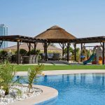 Shaded seating area with thatched gazebo and timber pergolas