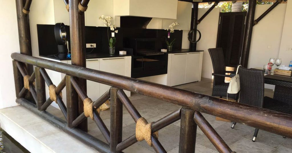 Outdoor kitchen with thatched roof and timber balustrades