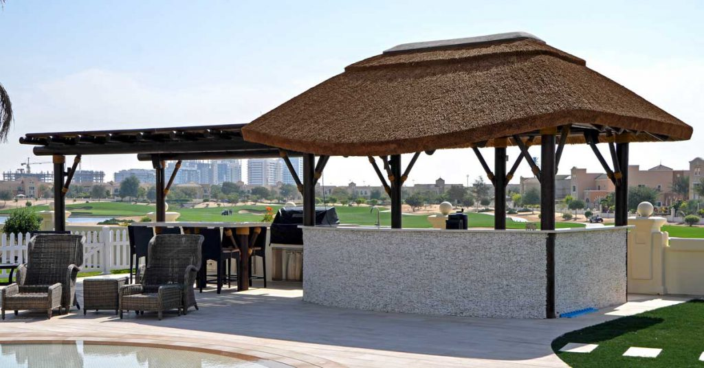 Outdoor kitchen with thatched roof gazebo and timber pergola