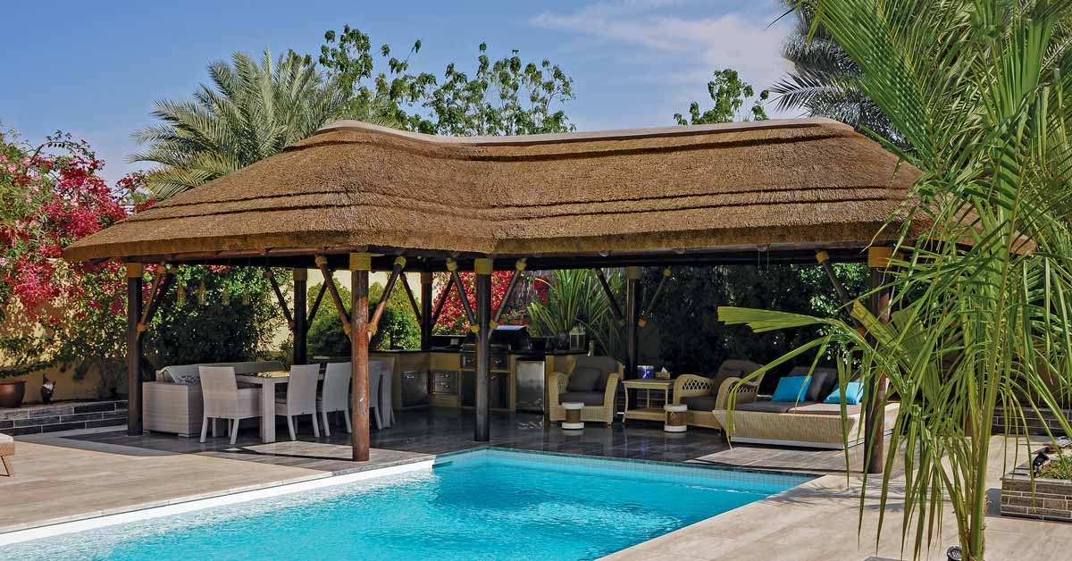 Thatched gazebo with dining area overlooking the swimming pool