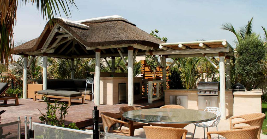 White washed thatched gazebo with outdoor kitchen, pergola and seating area in Arabian Ranches, Dubai