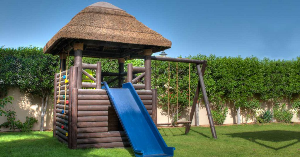 Eco-friendly playstructure with thatched roof, side climbing wall and swing