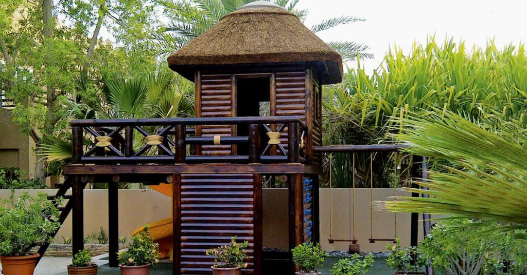 Eco-friendly playstructure timber climbing structure with thatched roof, swings and climbing wall