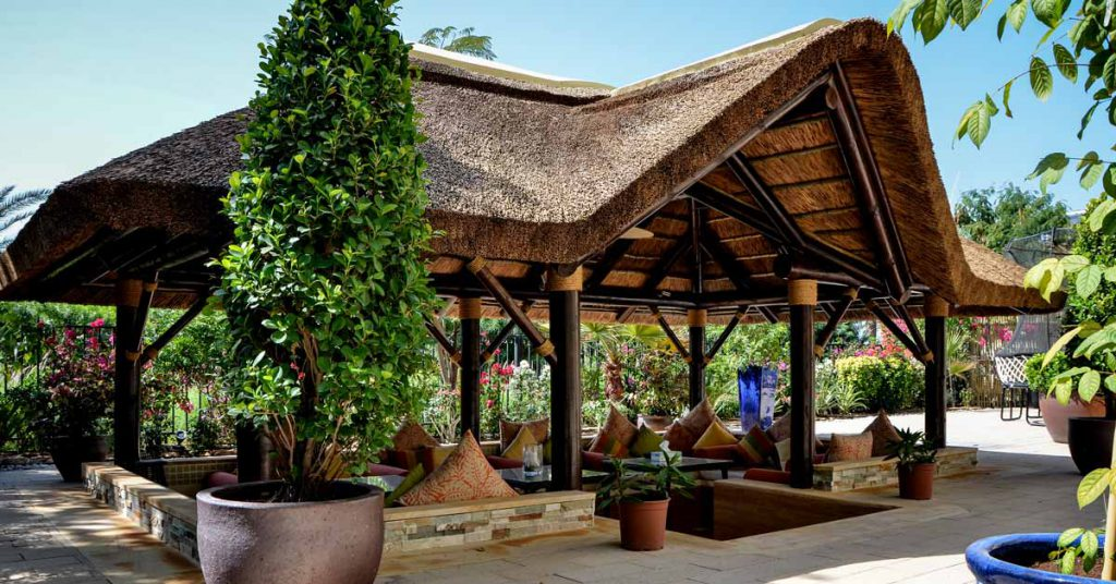 Spectacular outdoor transformation thatched gazebo with gable entrance and sunken seating area