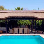 Poolside thatched gazebo with outdoor seating