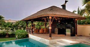Thatched gazebo with outdoor kitchen and seating area