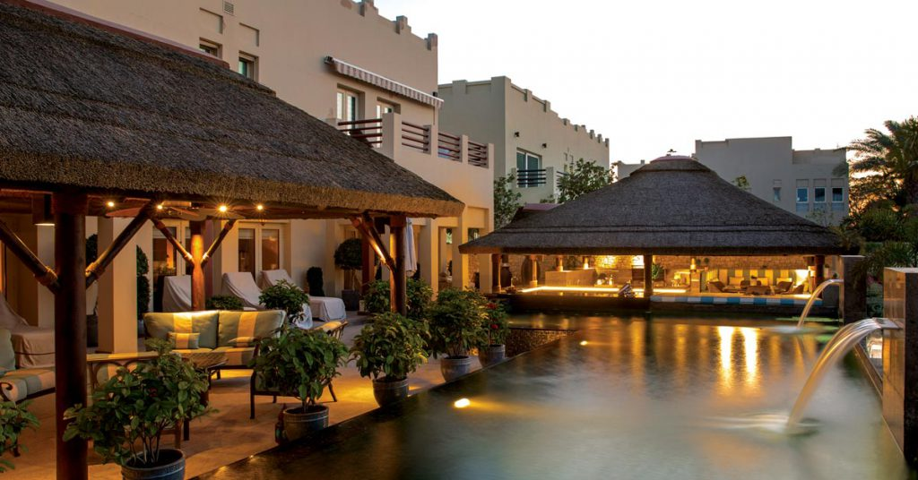 Thatched roof poolside with seating areas