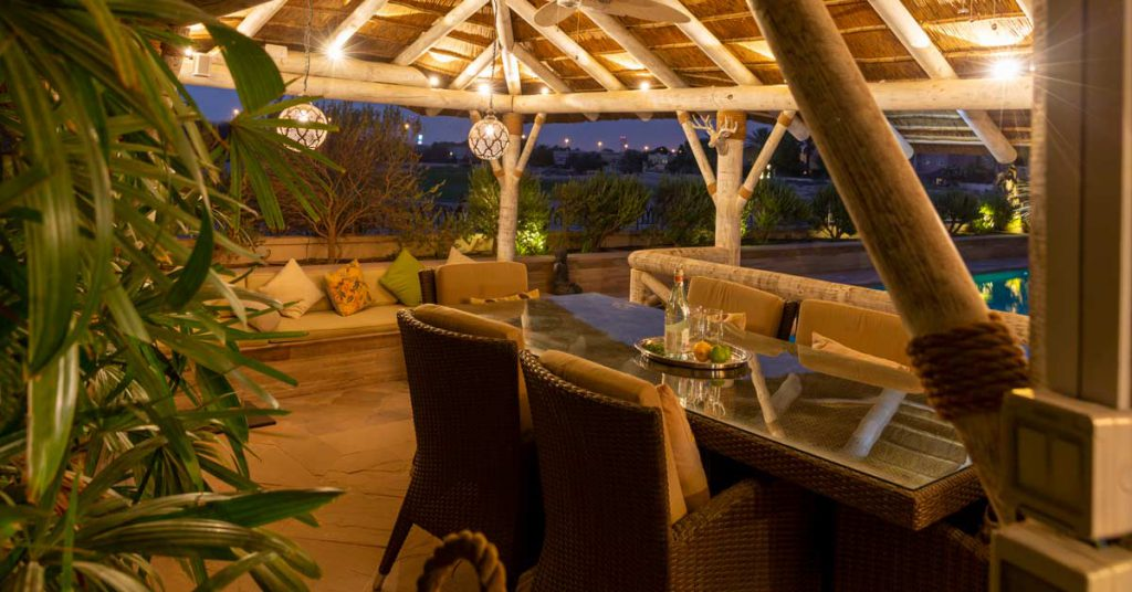 Outdoor dining under a modern thatched roof gazebo in a white wash finish