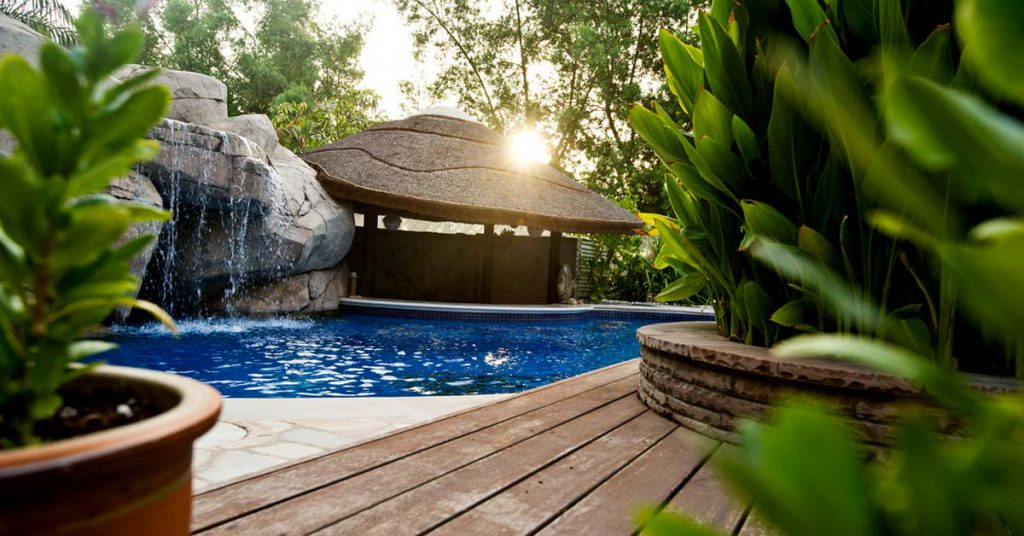 Thatched man cave with swim-up poolbar and timber decking