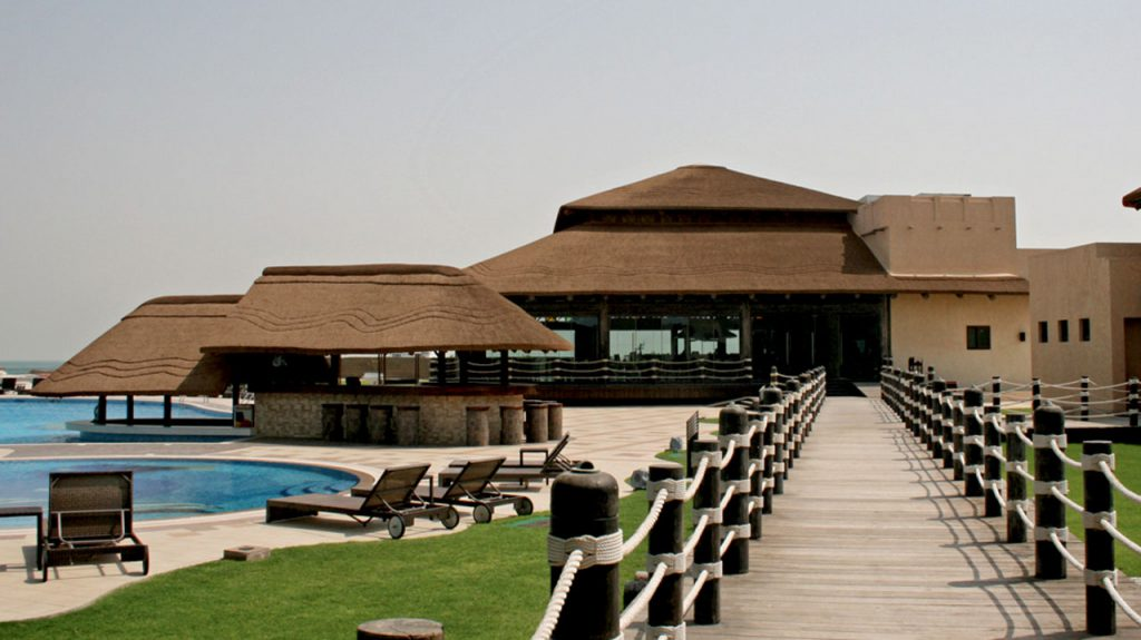 Al Maya Island timber decking walkway leading to the thatched restaurant