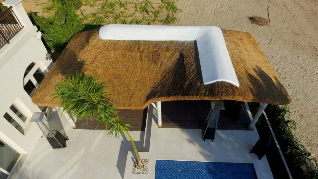 Outdoor living space with thatched roof poolside