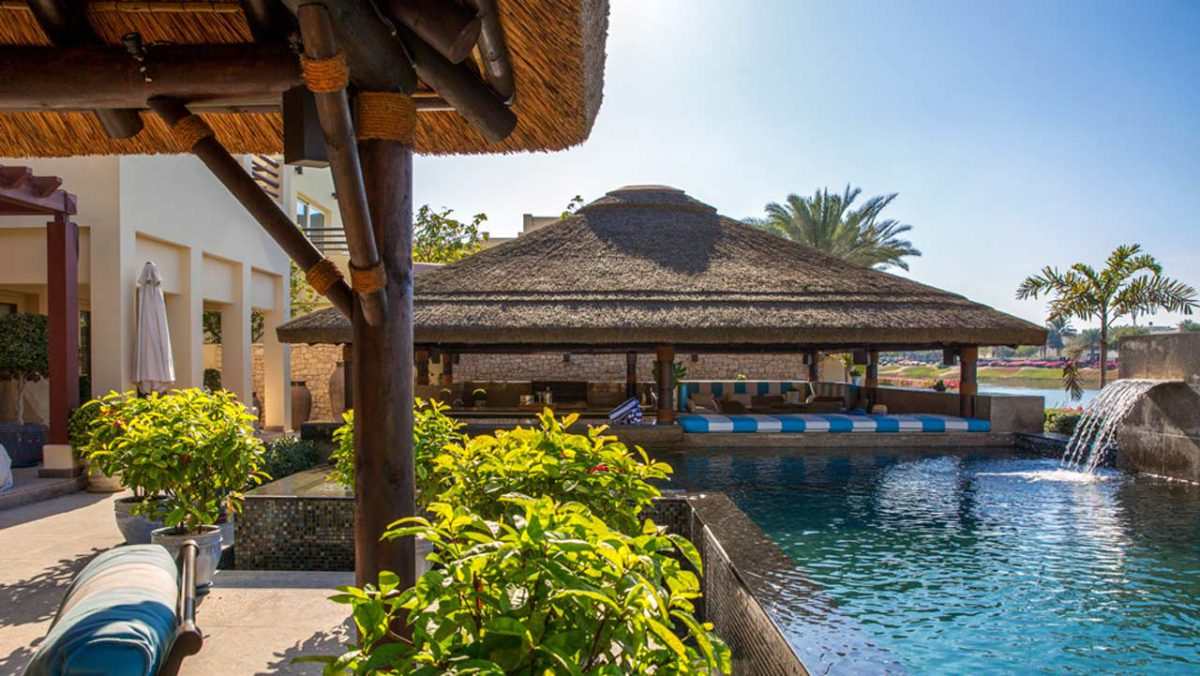 Thatched outdoor entertainment area with swim-up poolbar